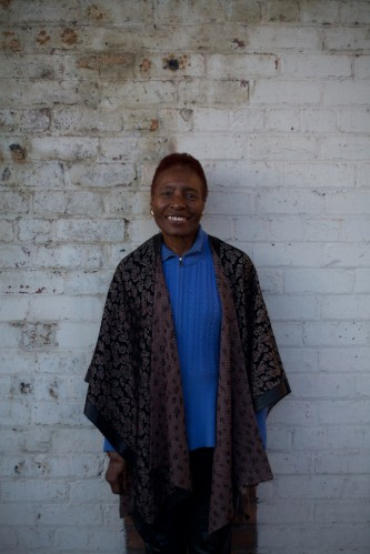 Hortense Spillers in blue and leather smiles at camera during a portrait