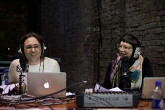 Terre and Laurence sit and smile with broadcast headphones on