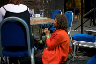 Reina Gossett in a red coat speaks into a mic whilst half under a table