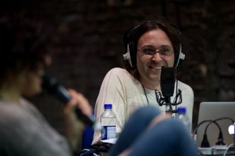 Terre Thaemlitz smiles cheekily with broadcast headphones on