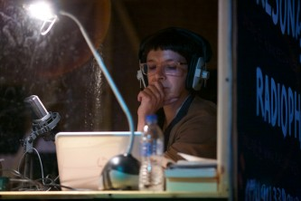 Laurence Rassel listens in a radio booth with broadcast headphones on