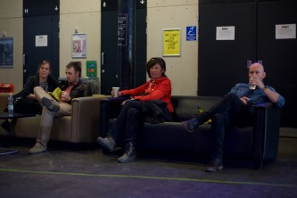 audience members sit on sofas in the tramway foyer