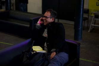An audience member calls in from the sofa and smiles whilst on their mobile