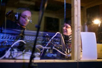 Terre and Laurence sit and smile in a large built radio booth