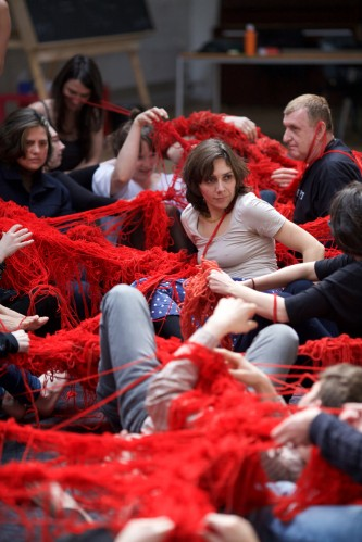 Participants move on the floor covered and tied together with red wool
