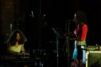 Someone with a multicoloured dress talks into a mic with a keyboard player