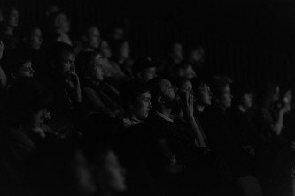 A dimly lit audience watching a film