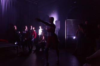 A strobe flash illuminates a performer surrounded by audience