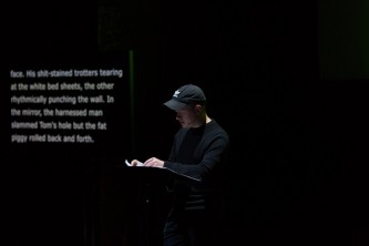 Huw Lemmey wearing a cap reading at a lectern at EPISODE 9