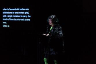 Jackie Wang reading from a lectern in front of a screen
