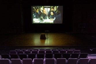 A scene from Robocop film projected in a theatre space