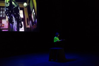 Jackie Wang reading in front of a projection of Robocop