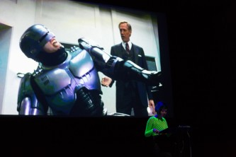 Robocop suffering on screen behind Jackie Wang reading on a stage