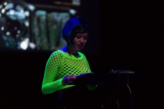 Jackie Wang reading from a lectern in front of a projected metallic surface