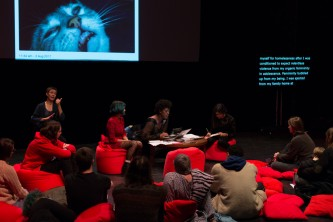 Projection of a cat's face, an audience, red cushions and a discussion