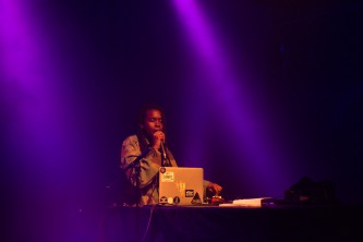 Moor Mother holding a microphone behind a laptop in purple light