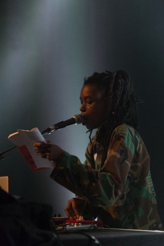 Moor Mother reading from a book into a microphone against grey light