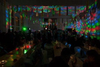 Coloured lights refracted around a dark space with people barely visible