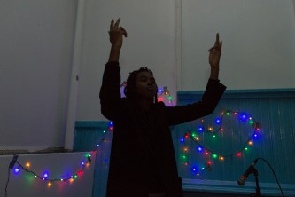 Moor Mother standing next to a mixer with arms raised, some coloured lights