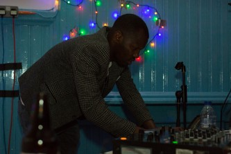 DJ Harsh operating some equipment in coloured light at Kinning Park Complex