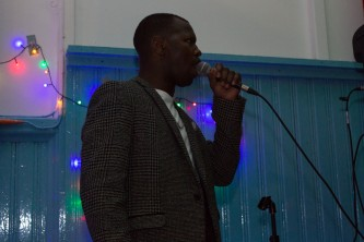 A man speaking into a microphone beside some coloured lights