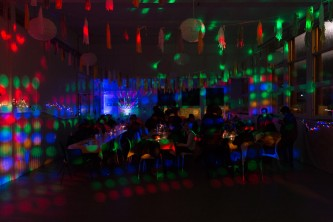 A room is covered with disco lights as people gather at tables