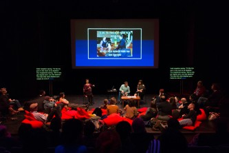 projection screen, speakers, audience members and red cushions