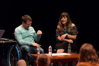 Robert Softley Gale laughing in a wheelchair next to Maxine Meighan on stage