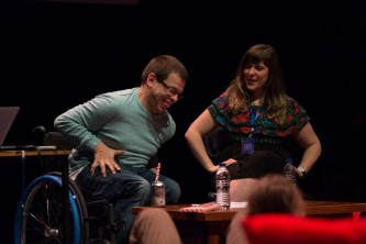 Two people laughing one in a blue jumper and the other in a patterned shirt