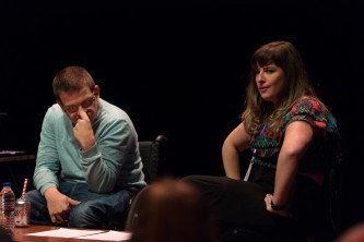 Maxine Meighan hands on thighs talking while Robert Softley Gale listens