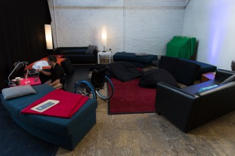 Robert Softley Gale seated in a studio space with a laptop and cushions