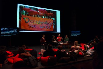 Projection of a poster, a discussion, audience, red cushions in a theatre
