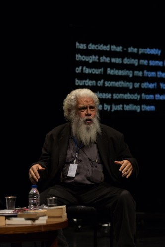 A bearded Samuel Delany speaking to an audience in a theatre