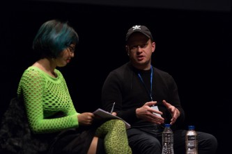 Huw Lemmey,  Jackie Wang sitting on stage talking by a table