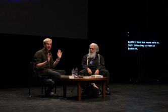 Barry Esson and Samuel Delany on stage by a small table with a screen behind