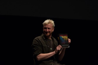 Barry Esson with quizical expression holding up a copy of a Samuel Delany book
