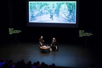 A screen showing a drawing behind Barry & Samuel on stage before an audience