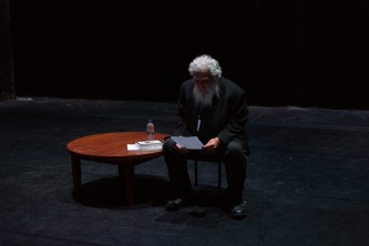 Samuel Delany reading from a document on stage; bearded with grey hair