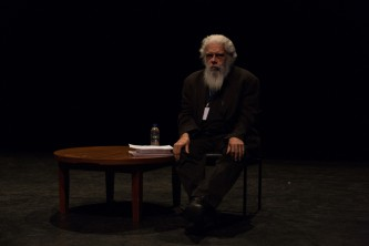 Samuel Delany seated next to a small table with a book and papers