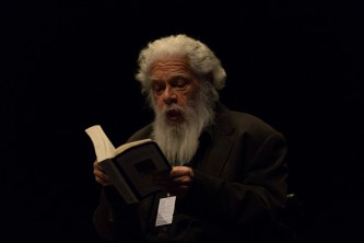 Samuel Delany wearing black and bearded reads from a book