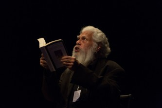 Samuel Delany looking upwards holding a book open