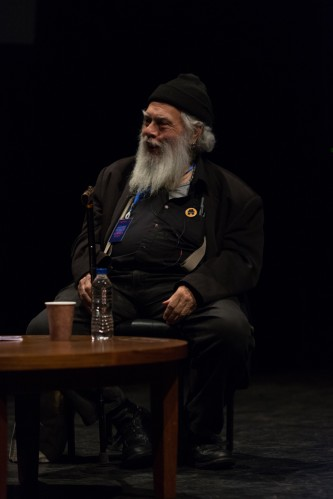 Bearded Samuel Delany wearing a little black hat smiling on stage by a table