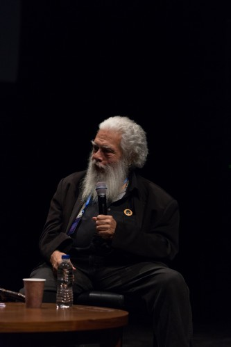 Samuel Delany holding a microphone on stage during a discussion