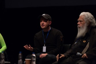 Huw Lemmey wearing a cap talking while Samuel Delany listens