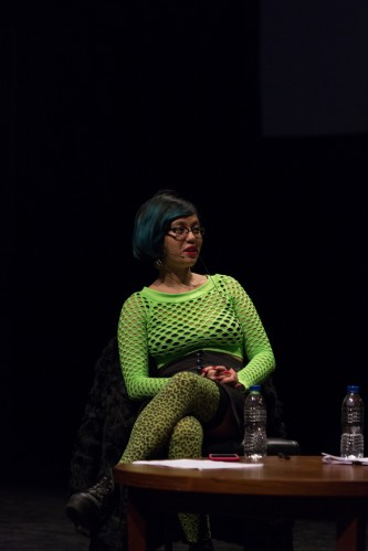 Jackie Wang wearing lime green and a headset mic next to a table