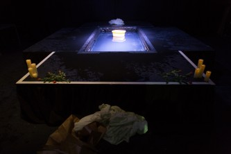 Sgàire's pool of water post performance with candles & grave-like accoutrements
