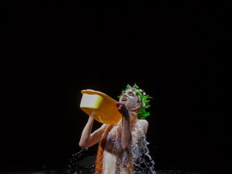 A plastic ivy wreath wearing figure pouring water over herself
