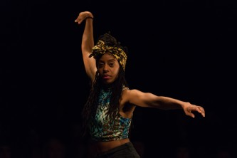 Mele Broomes dancing: prominant arms looking forwards mid performance