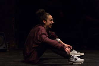 Claricia Kruithof sitting on the floor wearing trainers facing right smiling