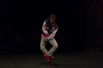 Storyboard P wearing a purple jacket dancing with red shoes and a hat